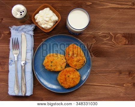 Rissoles Of Ham, Cheese  And Potatoes On Blue Plate, Milk In Glass, Pepper-pot And Sour Cream In Woo