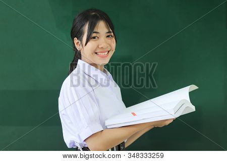 Smiling Happy Young Portrait Pretty Asian Student Girl Holding Book At Green Board In High School Or
