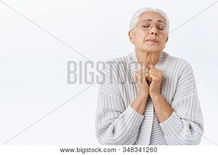 Dreamy And Overwhelmed Elegant Senior Woman Recall Youth Memories, Hold Hands Together Tight Near Ch