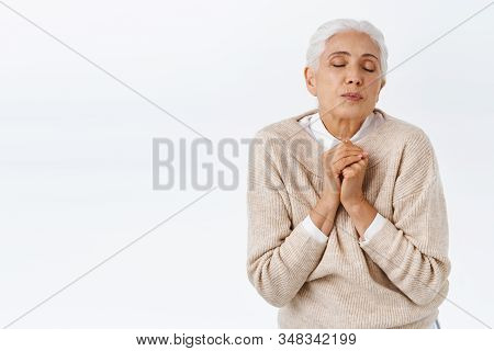 Romantic Elegant Senior Lady With Grey Combed Hair, Close Eyes, Fold Lips In Kiss And Press Palms To