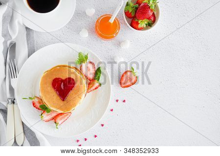 A Stack Of Pancakes With A Heart Of Jam On Top With Fresh Strawberries And Mint On A White Plate On