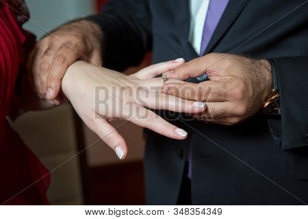 Wedding Hands Of A Bride And Groom . Groom Put A Ring On Finger Of His Lovely Wife. Young Man Puttin