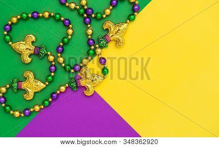 Mardi Gras Carnival Decoration Beads On Yellow Green Purple Background