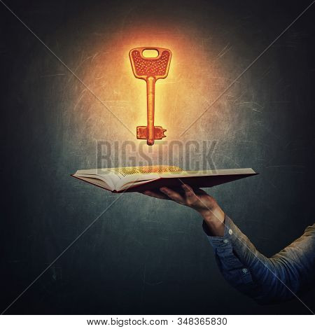 Male Student Hand Holding An Open Book With A Magic Shining, Golden Key Over A Dark Blackboard Backg