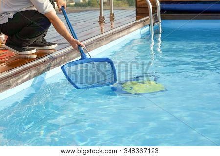 Hotel Staff Worker Cleaning The Pool. Pool Cleaner During His Work. Cleaning Robot For Cleaning The