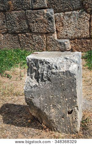 Ancient Greek Column In Delphi, Greece. Greek Script Carved On Surface