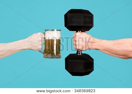 A Muscular Male Hand Holds Out A Heavy Dumbbell Towards A Glass With Beer In The Other Man S Hand. C
