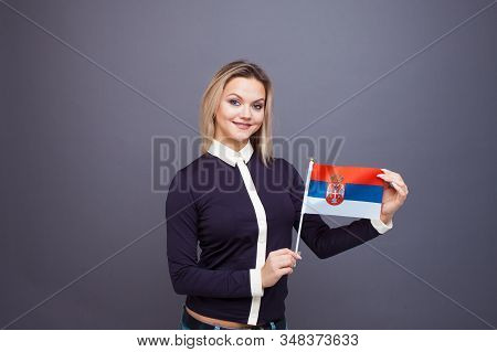 Immigration And The Study Of Foreign Languages, Concept. A Young Smiling Woman With A Serbia Flag In