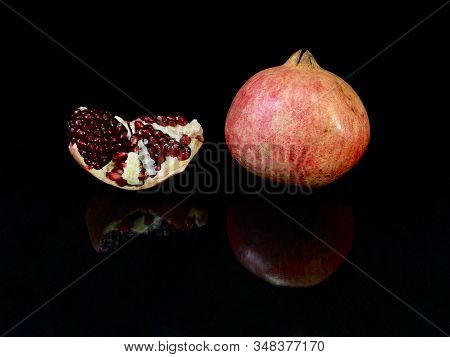 Juicy, Peeled Pomegranate On A Black Background. Large, Ripe Pomegranate Fruits. Concept: Fruit Diet
