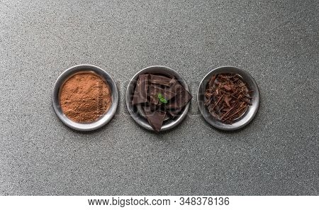 A Flat Lay View Of Dark Milk Chocolate, Cocoa Powder, And Chocolate Shavings.