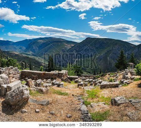 Temple Of Apollo Ruins In Delphi, Greece. Summer Scenic Landscape With Ancient Greek Carved Stones U