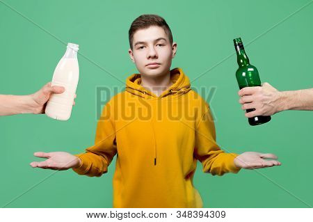A Teenager Is Faced With A Choice Of What To Use - Alcohol Or Milk. Hands Holding Out A Bottle Of Al