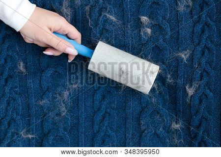 Woman Hand Using A Sticky Roller To Clean Fabrics - Woolen Knitted Sweater From Dust, Hair, Lint And