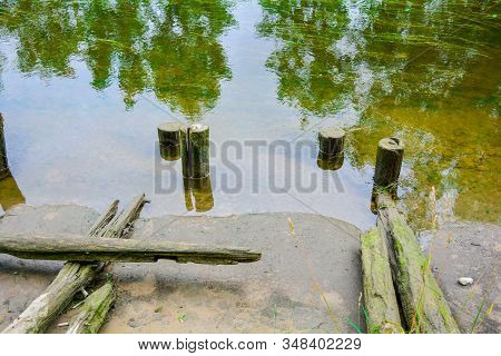 Sandy Shore And Old Weathered Wooden Posts In Reflective Water Of Shallow River Or Canal With Algae