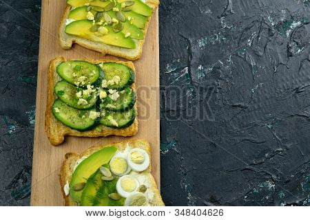 Three Sandwiches On A Wooden Board, A Mushroom Sandwich, An Avocado And Seeds Sandwich And A Sandwic