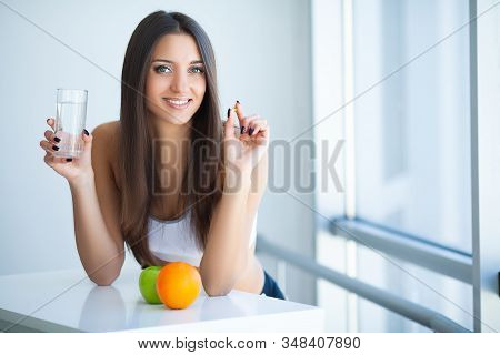 Beautiful Smiling Woman Taking Vitamin Pill And Dietary Supplement