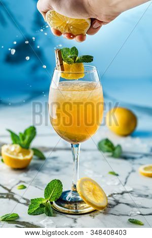 Fresh Lemonade With Mint, Lemon And Ice In Wineglass On Light Blue Background. Man Hand Squeezes Lim