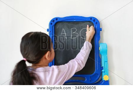 Little Asian Girl Writing Abc On Blank Black Board On White Background. Education Concept. Rear View