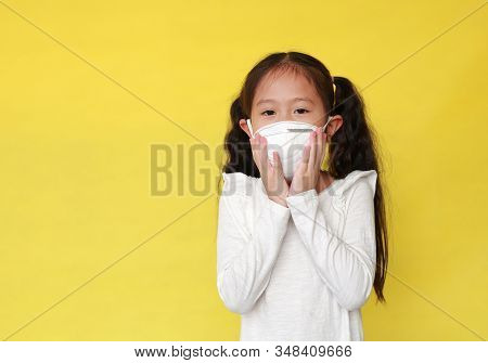 Portrait Of Asian Little Child Girl Wearing A Protection Mask For Against Air Pollution Isolated On