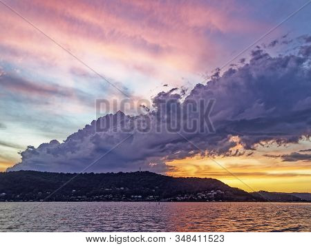 Colourful Stormy Pink And Yellow Coloured Cirrus Cloudy Coastal Sunset Seascape In A Blue Sky Over T