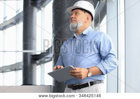 Mature Architect Wearing Hardhat Inspecting New Building.