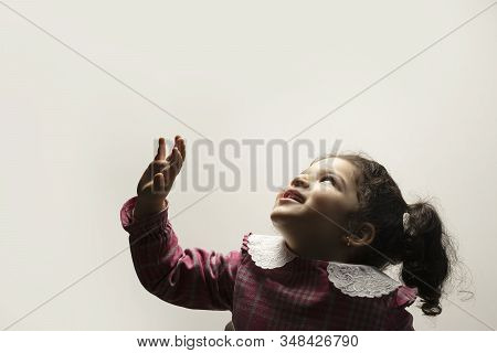 Happy Little Girl With Side Pony Hairstyle At Bottom Part Of Image Looking Up Of The Frame. Childhoo