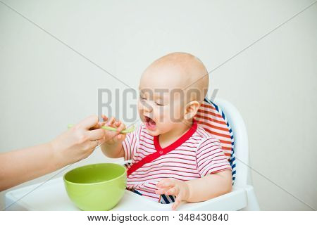 Cute Baby Eats With Spoon Sitting In Highchair