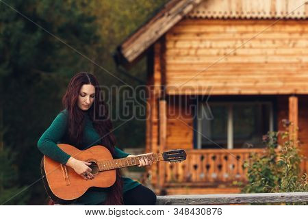 Long-haired Girl Plays Guitar Sitting On Parapet Near House.