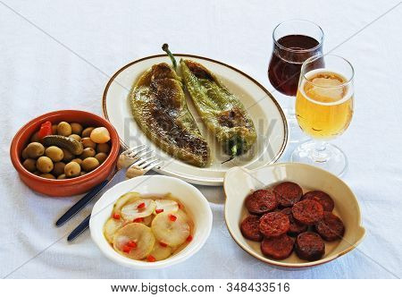 A Selection Of Tapas With Red Wine And Beer, Fried Pointed Green Peppers, Green Olive Cocktail, Pick