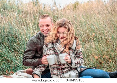 Young Couple In Love With A Hot Drink In Their Hands Laughing Joyfully Outdoors