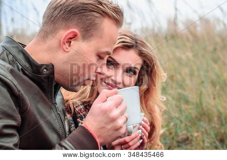 A Young Couple In Love Is Warming Themselves With Tea In Nature, The Girl Is Flirting At Her Lover,