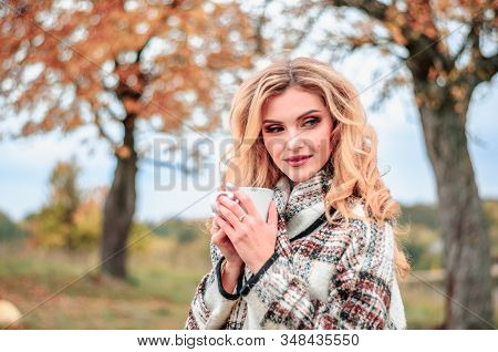 Beautiful Young Blonde Girl With A Cup Of Hot Tea In Her Hands Looks Thoughtfully To The Side Agains
