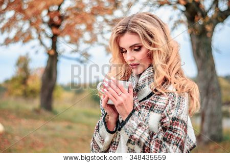 Beautiful Young Blonde Girl With A Cup Of Hot Tea In Her Hands Looks Thoughtfully Into A Cup On An A
