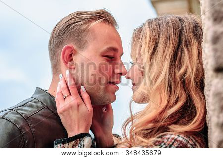 Happy Romantic Couple In Love Kisses Outdoors Near The Old Building On A Cold Autumn Day, Concept Of