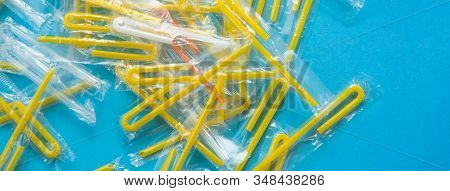 Pile Of Yellow Drinking Straws On A Blue Background. Top View Of Many Plastic Bendy Cocktail Straws