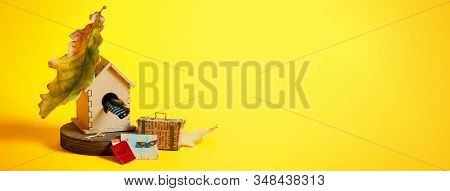 Wooden Bird House With Suitcase, Map, Pasport And Ticket On A Bright Yellow Background. Social Media