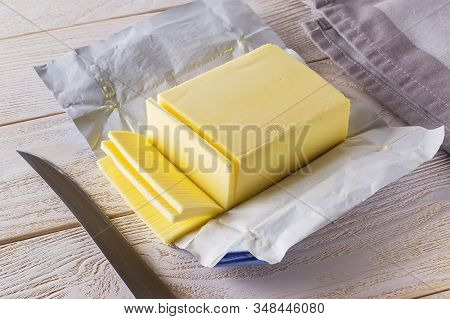 Slices Of Fresh Yellow Butter Cut Off From A Just Opened Pack And Knife On A White Wooden Table. Dai