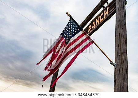 A Woven Usa Flag Flies In The Entrance Arch Of A Ranch In Oregon, Usa