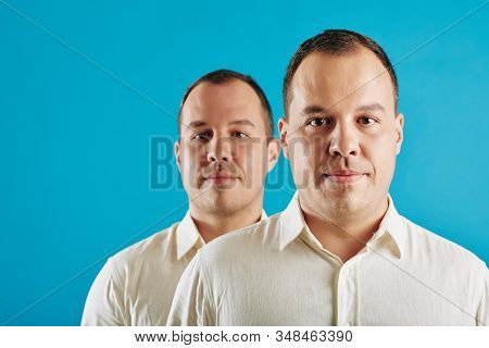 Conceptial Portrait Of Young Adult Caucasian Man Wearing White Shirt Standing Behind His Twin Brothe