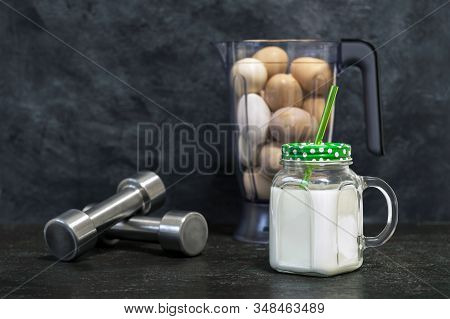 Protein Shake In A Mug On The Background Of A Blender Bowl With Chicken Eggs And Dumbbells On A Dark