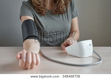 Woman Measuring Blood Pressure Herself With A Digital Pressure Gauge. Health Care And Medical Concep