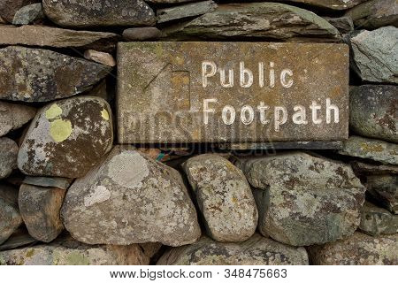 Stone Public Footpath Sign.  The Stone Public Footpath Sign Is Embedded In A Dry Stone Wall And Is S
