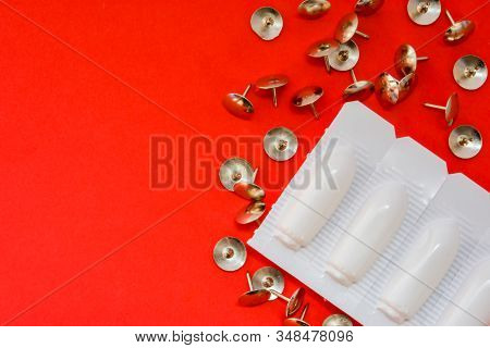 Thumbtacks, Rectal Suppositories In Packing On Red Background. Medical Concept Of Sign And Symptoms