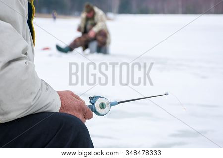 The Fisherman Sits With Winter Fishing Rod In Hand In The Foreground, In The Background Blurred Silh