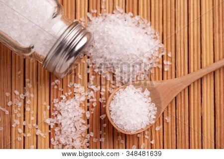Salt Sprinkled On The Table. Spoon With Salt And Salt Shaker. Salt Crystals On A Wooden Table Surfac