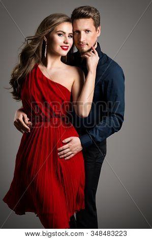 Couple Fashion Beauty, Beautiful Woman In Red Dress And Elegant Man Studio Portrait