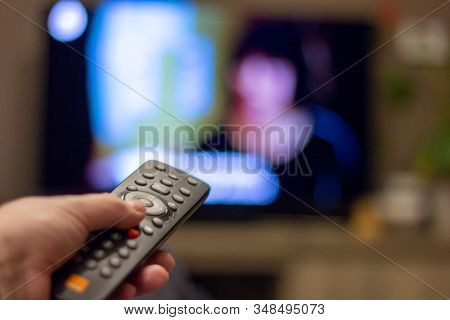 Brecht, Belgium - November 14 2019: A Hand Holding A Television Remote Control With In The Backgroun