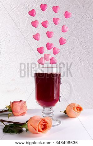 Glass Of Red Wine With Roses And Hearts On White Background.