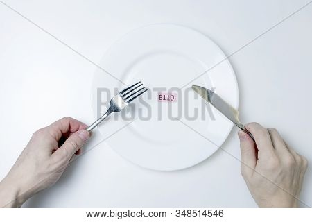 Harmful Food Additives. Mens Hands Hold A Knife And A Fork. On The Plate Is A Plate With The E-addit