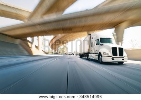 American style truck on freeway pulling load. Transportation theme. Road cars theme. Truckers heaven. Truck passing the bridge